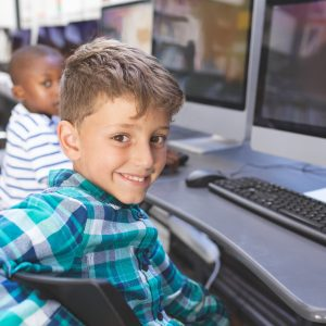 Portrait of happy schoolboy sitting on chair and looking at camera in computer room